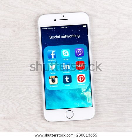 SIMFEROPOL, RUSSIA - NOVEMBER 11, 2014: Apple iPhone 6 over table displaying social networking applications. The iPhone 6 and iPhone 6 Plus are smartphones running iOS developed by Apple Inc. - stock photo