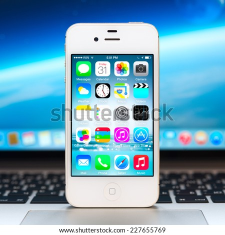 SIMFEROPOL, RUSSIA - NOVEMBER 01, 2014: Apple iPhone stay over Macbook and displaying iOS 8.1 homescreen. iOS 8 is the eighth major release of the iOS mobile operating system designed by Apple Inc. - stock photo