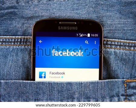 SIMFEROPOL, RUSSIA - NOVEMBER 11, 2014: Samsung Galaxy S4 in jeans pocket displaying Facebook application. Facebook is largest and most popular social networking site in the world. - stock photo