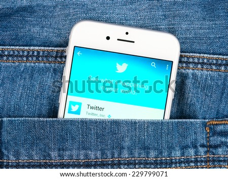 SIMFEROPOL, RUSSIA - NOVEMBER 11, 2014: Silver Apple iphone 6 in jeans pocket displaying Twitter application. Twitter is an online social networking service that send and read messages - stock photo