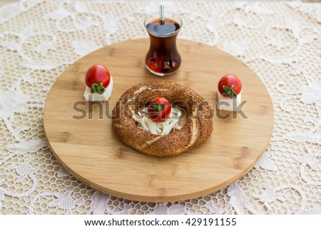 simit, tea, cherry tomato and cheese at balcony on a circle wooden plate top view - stock photo
