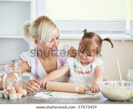 Simper mother and child baking cookies in the kitchen - stock photo
