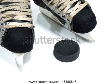 Simple amateur hockey skates and the puck - stock photo