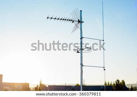 simple antenna mast with antennas to receive digital TV and radio signals, DVB-T, DVB-T2 and FM (horizontal polarization) including delayed lightning rod. In the background the peaks of roofs. - stock photo