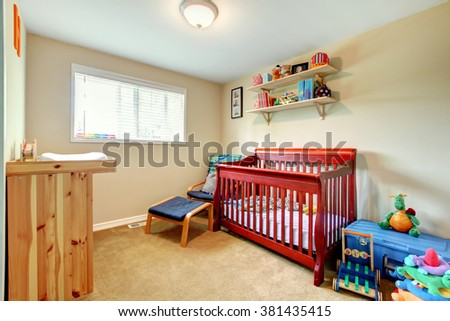 Simple baby bedroom with nice crib and carpet. - stock photo