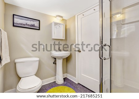 Simple bathroom interior with purple floor and light beige walls. White washbasin stand and toilet