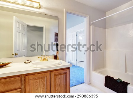 Simple bathroom with full bath shower, connected to bedroom.