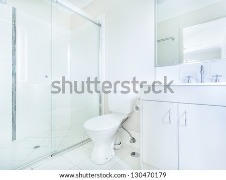 Simple bathroom with sink, mirror, toilet and shower - stock photo