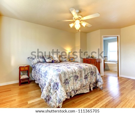 Simple bedroom with flowery bedding and hardwood floor with bathroom view.