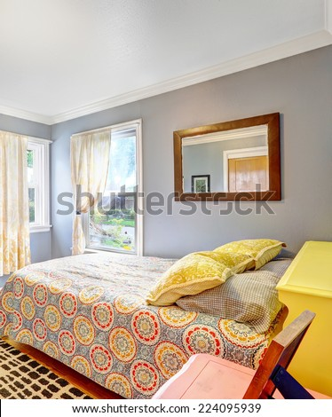 Simple bedroom with light blue walls. Bed decorated with yellow pillows - stock photo