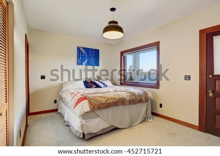 Simple bedroom with one bed, carpet floor and white walls with brown trim