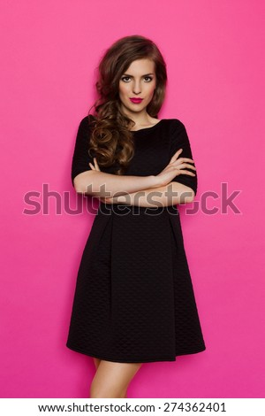 Simple Black Dress. Elegance woman in black mini dress standing with arms crossed. Three quarter length studio shot on pink background. - stock photo