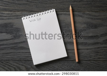 simple blank notepad with phrase wish list on rustic wood table, background - stock photo