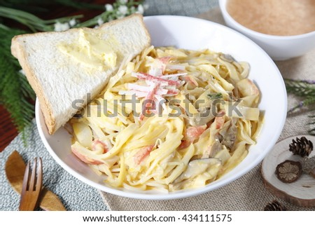 Simple bowl of chinese noodle with sandwich on the table - stock photo