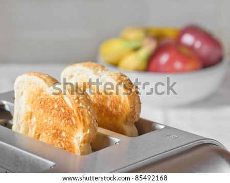 Simple breakfast scene of toast in a toaster with a bowl of fruit behind - stock photo