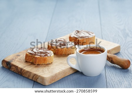 simple breakfast with cup of espresso and baguette slices with chocolate spread - stock photo