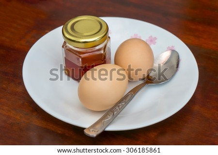 simple breakfast with honey and fresh egg - stock photo