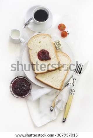 Simple breakfast with slice of plain sandwich loaf bread served with jam and butter. Over head table top view. - stock photo
