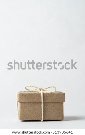 Simple brown box with closed lid, tied to a bow with string, signifying a gift, surprise or secret.