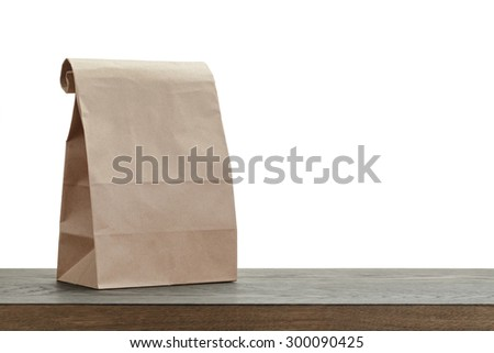 simple brown paper bag for lunch or food on wooden table - stock photo