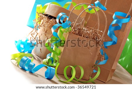 Simple brown paper gift bags and boxes decorated with colorful curling ribbon.  Bright white background. - stock photo