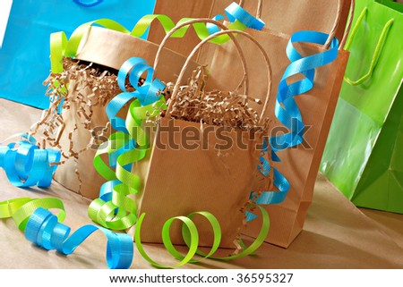 Simple brown paper gift bags and boxes decorated with colorful curling ribbon.  Close-up with shallow dof. - stock photo