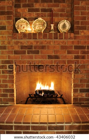 Simple clean brick fireplace with a single fire log burning out to give heat. There are Christmas plates decorating it at the top, but those can be cropped out to remove any holiday type theme. - stock photo