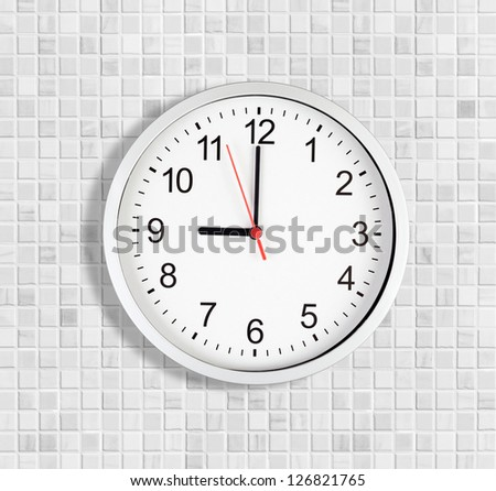 Simple clock or watch on white tile wall displaying nine o'clock - stock photo