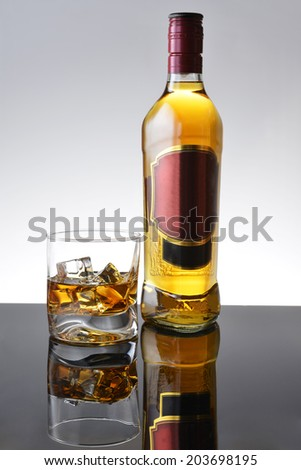Simple composition of glass and bottle whisky. - stock photo