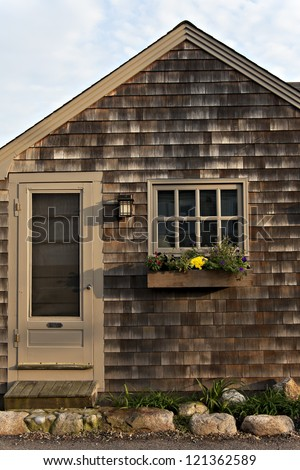 Simple craftsman style cottage with wood shingles and flower-filled window box.