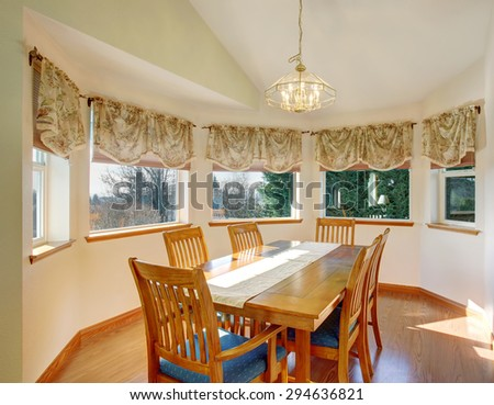 Simple dinning room with hardwood floor and lots of windows.