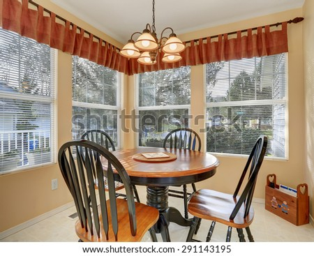 Simple dinning room with tile floor, and windows.