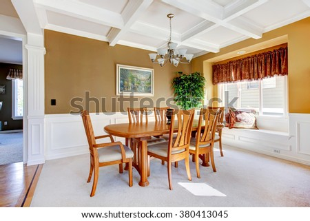 SImple dinning room with white carpet and beige walls.