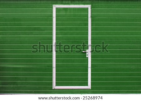 simple door in green wall - stock photo