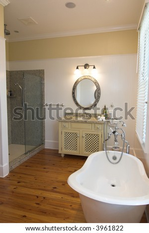 simple elegant bathroom with clawfoot tub and glass shower