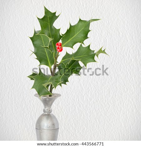 Simple festive decoration. Sprig of green holly in silver vase, with red berries. Textured background for vintage, traditional effect. Christmas, seasonal. - stock photo