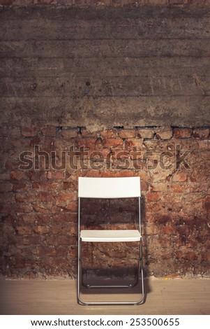 Simple folding-chair near the grungy brick wall - stock photo