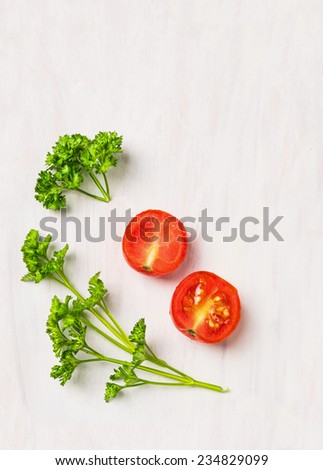 Simple food  background, parsley and tomato on white wooden table - stock photo