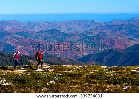 Simple Healthy Lifestyle Concept Image of Two Hikers walking in Mountains Man and Woman going along Mountain Crest Bright Colors sporty Clothing Backpacks Autumnal Trees Forest on Background - stock photo