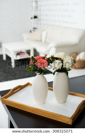 Simple home interior decoration, vase of flowers on a table in the interior of modern apartment