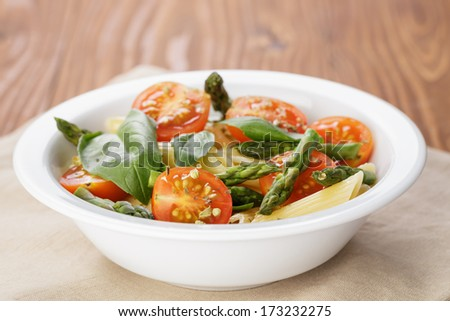 simple italian pasta penne with tomatoes and basil, on table - stock photo