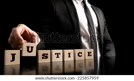 Simple Justice Concept - Close up Businessman in Black Business Suit Arranging Small Wooden Pieces with Justice Text on Black Background. - stock photo