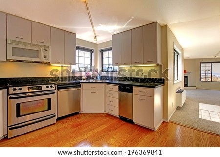 Simple kitchen interior with white storage combination and steel appliances.
