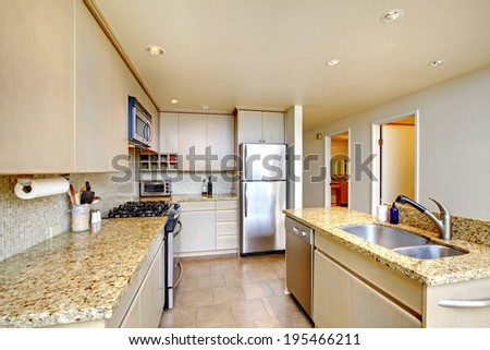 Simple kitchen room with tile floor and light tones cabinets - stock photo