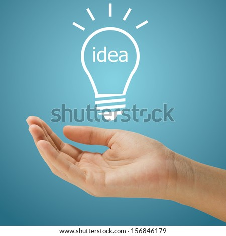 simple lightbulb with idea word floating on women hand on blue background - stock photo