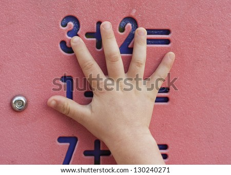 Simple maths or mathematics counting exercise on a toy board with a child's hand pointing.