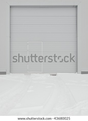 simple metal door in gray wall - stock photo