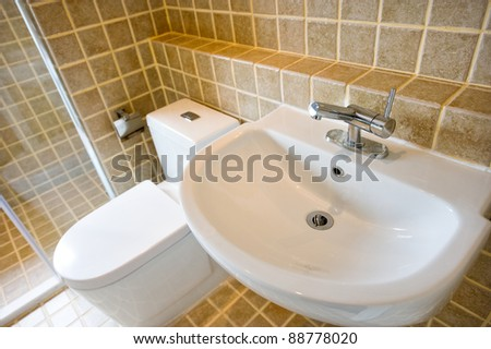 Simple modern bathroom with toilet, sink, and tile floor. - stock photo