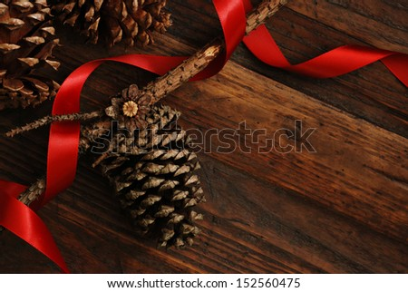 Simple, natural Christmas decor of pine cones with red satin ribbon on rustic, dark wood background.  Low key still life with directional, natural lighting for effect.  - stock photo