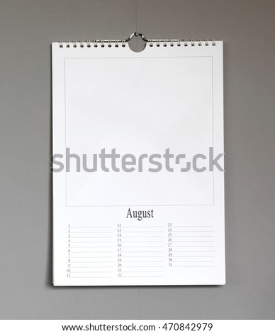 Simple old birthday calendar hanging on a grey wall, copy space - August